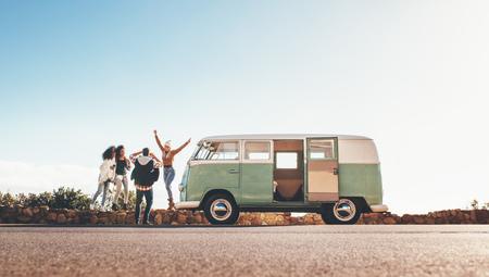 Groep man en vrouwen op road trip samen. Oude minibus geparkeerd op snelweg met vrienden fotograferen buitenshuis. Man die foto's van vrouwelijke vrienden nemen die zich op dijk bevinden. Stockfoto