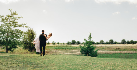 Beautiful wedding couple with groom lifting up his bride at park. Rear view of groom carrying the bride at park.