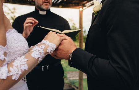 Close up of bride and groom holding each others hands during outdoor wedding ceremony. Priest performing a wedding ceremony for couple outdoors. Stockfoto