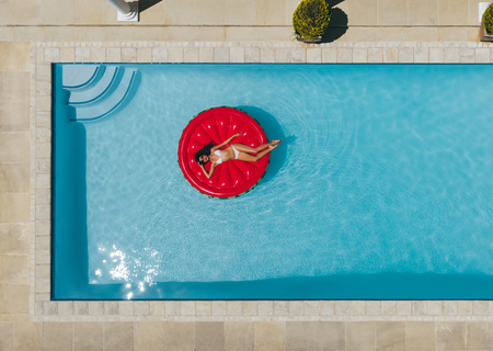 Woman relaxing on big red floating mattress in the pool water on hot sunny day. Female enjoying summer holidays. Top view.