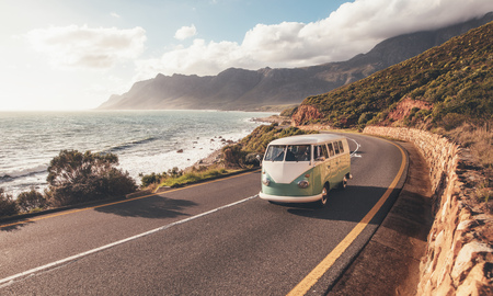 Mini van on coastal road. Group of friends traveling by a van on highway along the sea.