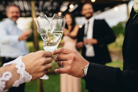 Close up of new married couple toasting champagne glasses at wedding party. Bride and groom hands clinking glasses at wedding reception. Фото со стока