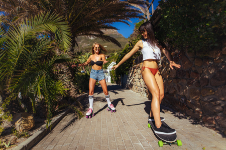 Smiling female friends skating during their summer vacation. Women in bikini doing skateboarding on a small path. Banque d'images