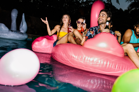 Group of men and women sitting on inflatable pool mattress. Friends enjoying in a pool in evening. Evening pool party. Banque d'images