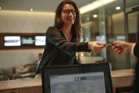 Asian businesswoman receiving key card for hotel room at reception. Female guest taking room key card at check-in desk.