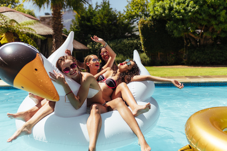 Group of friends on vacation having fun on an inflatable swan in swimming pool. Multi-ethnic women friends enjoying their holidays in a pool at resort.