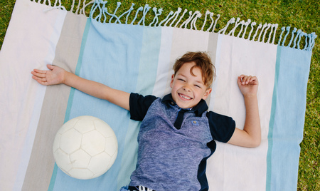 Cheerful boy lying on the ground with a football by his side. Top view of a boy lying on a blanket laid out in a park.