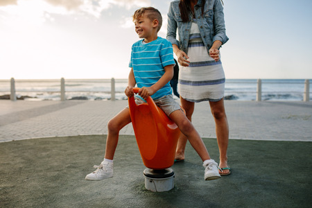 Boy enjoys sitting on a rotating chair near seafront. Woman with her son on a vacation enjoying near the sea. Stock Photo