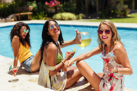 Diverse group of female friends sitting by the resort swimming pool having cocktails and smiling. Women having a poolside party on a summer day. Stockfoto