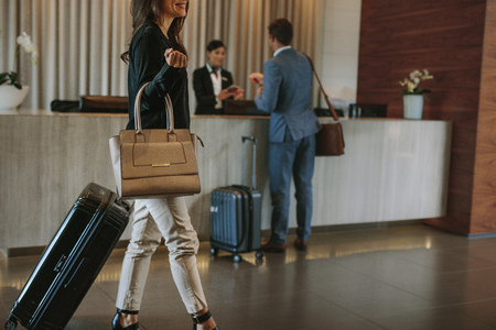 Female guest walks inside a hotel lobby with people in the background at reception counter. Woman arriving at hotel.