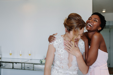 Cheerful young bride and bridesmaid on the wedding day in hotel room having fun. Happy gorgeous bride in white dress having fun with bridesmaid.