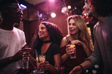 Grupo diverso de jóvenes con bebidas en un club. Hombres y mujeres felices disfrutando de nightout en el bar. Foto de archivo