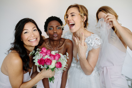 Portrait of cheerful bridesmaids with the bride in the room in the morning. Gorgeous bride in white dress having fun with beautiful bridesmaids in hotel room.