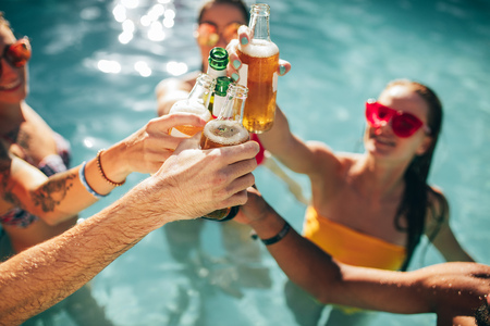 Group of friends toasting at party in swimming pool. Young people in the pool having beers. Focus on beer bottles in hands.