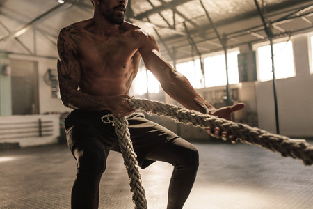 Male bodybuilder pulling rope at cross training gym. Male athlete doing exercises with rope at gym.