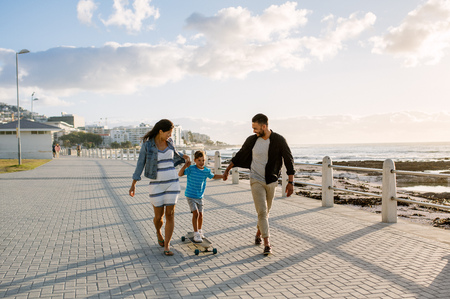 Cheerful family on vacation enjoying outdoors. Happy couple holding hands of the child while the boy moves along on a skateboard.