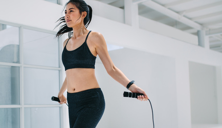 Female doing fitness training with jump ropes at health club. Fitness woman skipping ropes at gym.