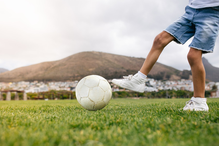 Close up of boy kicking a football in a playground. Low angle view of a boy playing football in a playfield.