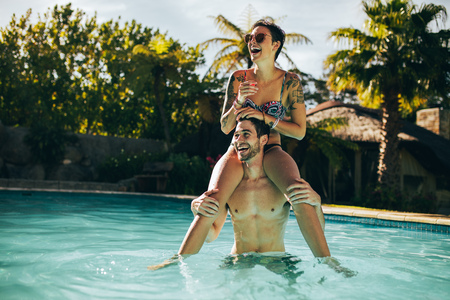 Handsome young man carrying his beautiful girlfriend on his shoulder and laughing inside a pool. Young couple having fun in swimming pool.