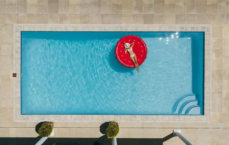 ビキニ姿の女性が、帽子をかぶった顔でスイミングプールのフローティングマットレスの上に横たわっている様子。プールでインフレータブルマッ