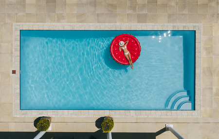 Aerial view of female in bikini lying on a floating mattress in swimming pool with her face covered with hat. Top view of woman sunbathing on inflatable mattress in pool. Archivio Fotografico