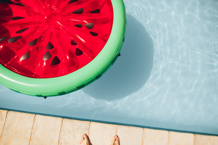Top view of colorful inflatable watermelon floating mattress in a swimming pool on a summer day. 版權商用圖片