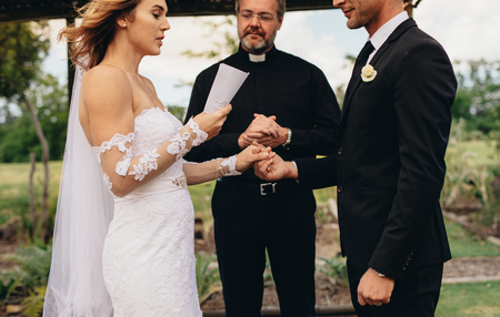 Bride holding a paper and reading wedding vows, with minister standing in the background. Couple exchanging vows on wedding ceremony. Stock Photo