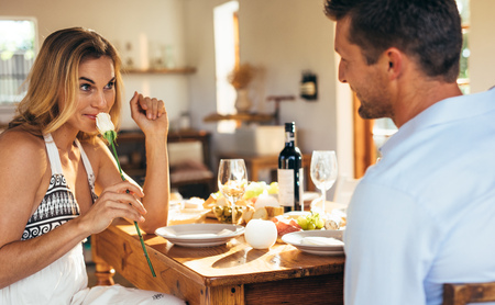 Woman smelling the rose given by her boyfriend at dining table. Couple having romantic dinner at home.