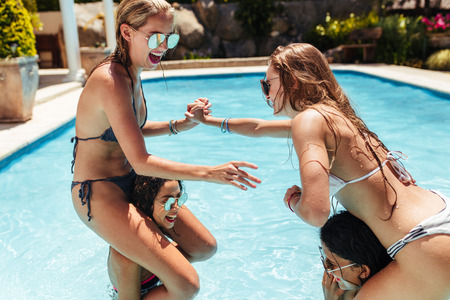 Women in bikinis having fun in swimming pool. Girls sitting on their friends shoulders and fighting in a pool.
