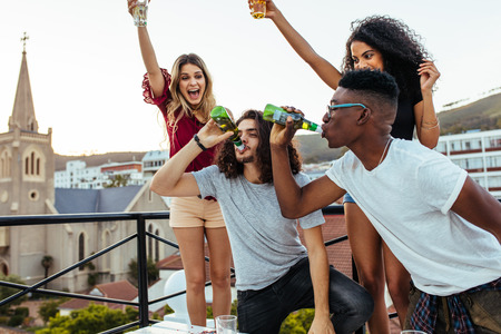 Multiracial young people partying on terrace, with men drinking beers together and girls cheering. Beer drinking challenge at rooftop party.