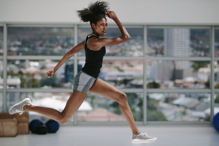 Fitness woman exercising at gym. Female doing intense physical workout in fitness studio. Stock Photo