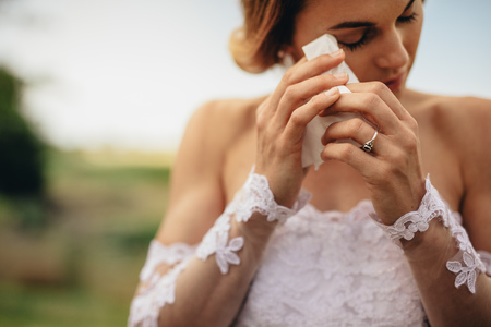 Beautiful bride in white dress weeps tears of happiness on the wedding day. Emotional woman in wedding gown wipes the tears with tissue paper. Banque d'images