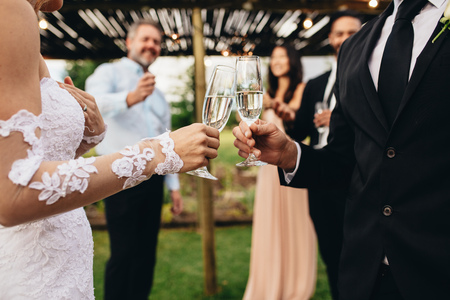 Bride and groom making a toast with champagne glasses after wedding ceremony with guest enjoying in background. Close up of newlywed couple having drinks at wedding party.