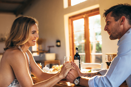 Loving young couple sitting at dining table holding each others hands. Man and woman having a romantic dinner at home.