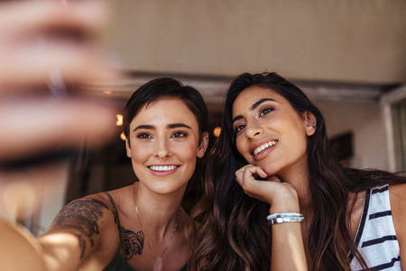 Two women sitting outdoors looking at a mobile phone. Smiling women posing for a selfie.