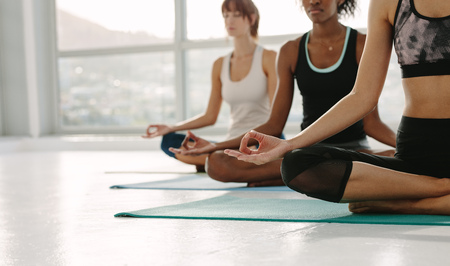 Cropped shot of fitness women practising yoga, sitting on floor with legs crossed and hands on knees. Group of people meditating in lotus yoga pose at gym class. Stock Photo