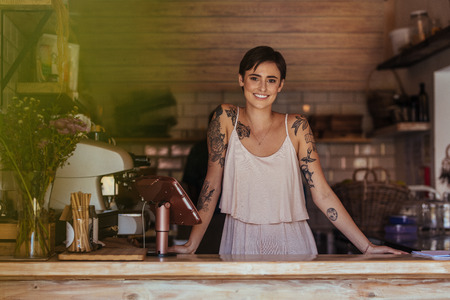 Woman standing at the counter of her cafe posing. Smiling restaurant owner standing beside the billing machine. Archivio Fotografico