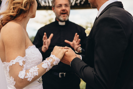 Cropped shot of couple holding hands and exchanging vows on their wedding day. Bride and groom getting married in front of a priest.