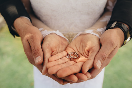 Close up of two wedding rings on bride and grooms palms. Bride and groom holding wedding rings on their palms during ceremony. Stock Photo