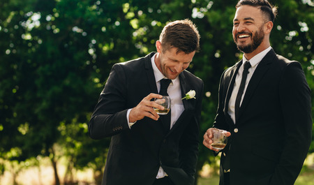 Groom and best man drinking and smiling during wedding party. Groom and groomsmen partying after wedding.