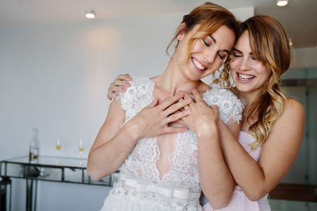 Smiling bridesmaid giving a tender hug to beautiful bride on her wedding day. Woman embracing her friend in wedding gown in hotel room.