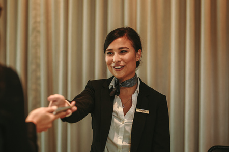 Female guest paying with mobile phone in hotel at the reception during check-out. Female receptionist receiving payment for hotel room from client in hotel. 版權商用圖片