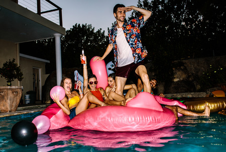 Group of friends having party in a pool in evening. Young people on air mattress in pool enjoying party.