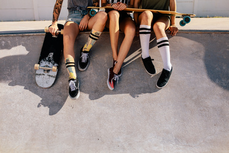Legs of women sitting on ramp at skate park. Cropped shot of female skaters resting on ramp after skateboarding. Archivio Fotografico - 99065780