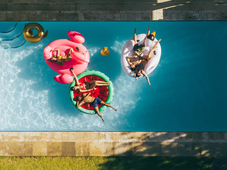 Aerial view of group of friends relaxing on a inflatable mattresses in pool. Happy young people chilling on air mattresses in swimming pool. 版權商用圖片 - 98831064