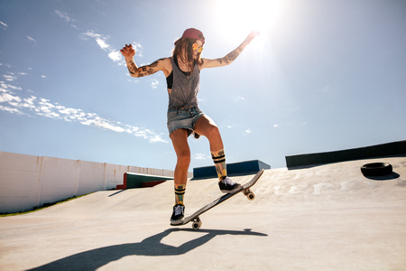 Female skater skateboarding at skate park. Women doing tricks on skateboard. Archivio Fotografico - 99065803