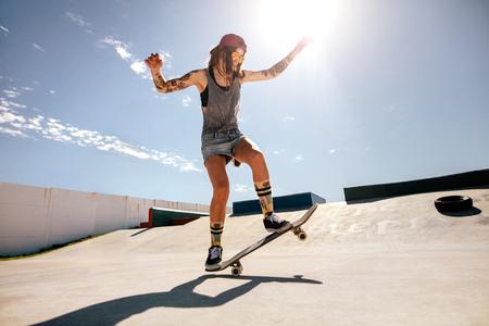 Female skater skateboarding at skate park. Women doing tricks on skateboard.