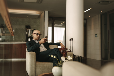 Business traveler waiting in airport lounge and using mobile phone. Businessman waiting for fight at airport lounge.