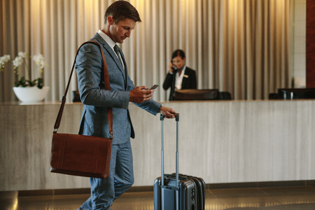 Young businessman walking in hotel lobby and using mobile phone. Business traveler arriving at his hotel.
