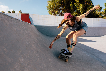 Skater female rides on skateboard at skate park ramp. Young woman practising skateboarding outdoors at skate park.